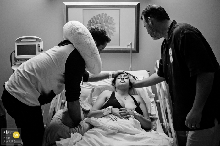 A family supports a woman in the hospital as she prepares to give birth in this black and white photo by a Key West, FL birth photographer.