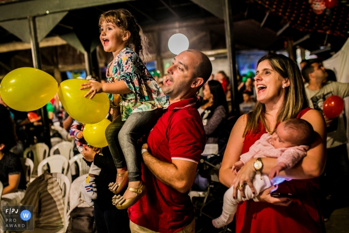 A mother holds her sleeping baby while a father holds his daughter as they cheer in this Family Photojournalist Association awarded photo by a Rio de Janeiro documentary family photographer.
