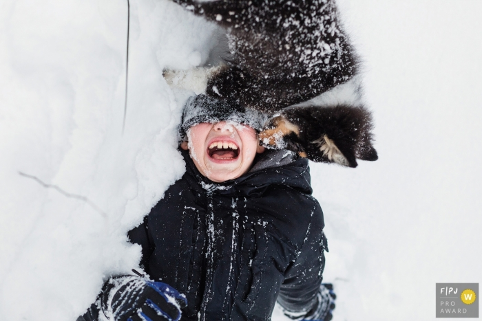 A boy plays in the snow with his puppy in this photo recorded by a Saint Petersburg, Russia award-winning, documentary-style family photographer.