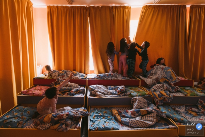 Several children wake up and get out of their tiered beds in the morning in this photo by a Saint Petersburg, Russia award-winning family photographer.