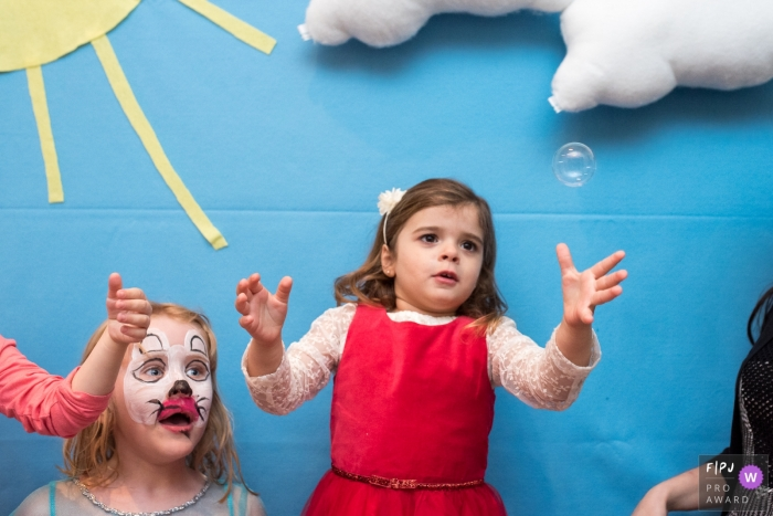 A young girl tries to pop a bubble while a girl with her face painted watches in this photo by a Lisbon, Portugal family photojournalist.
