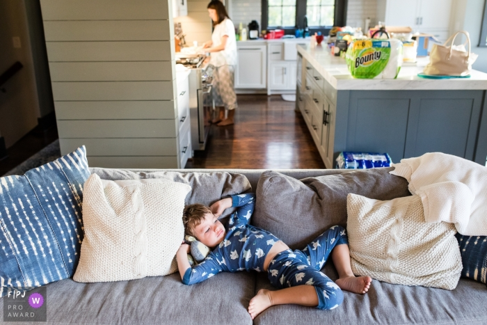 A boy lays sprawled on the couch as his mother cooks in the kitchen in this photo by a Missoula, MT family photojournalist.