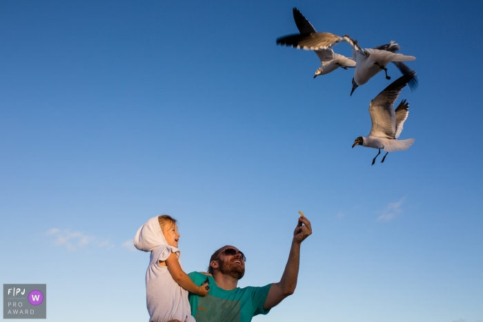 A father holds his daughter as he tries to feed seagulls in this photo by a Missoula, MT family photojournalist.