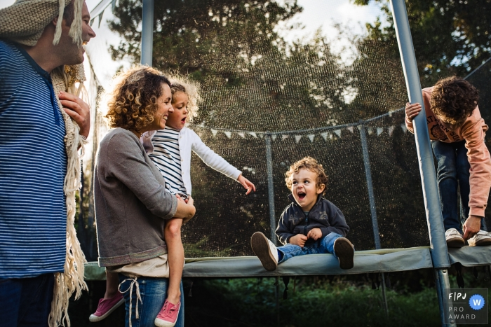 A mother and father laugh as their son sits on a trampoline in this photo by a Wallonie family photojournalist.