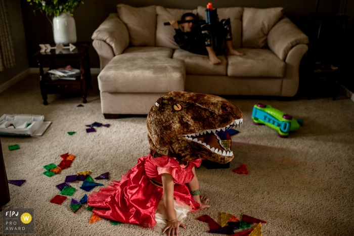 A little girl in a princess dress wears a T-Rex head as her brother sits on the couch in this photo by a Spokane, WA family photojournalist.