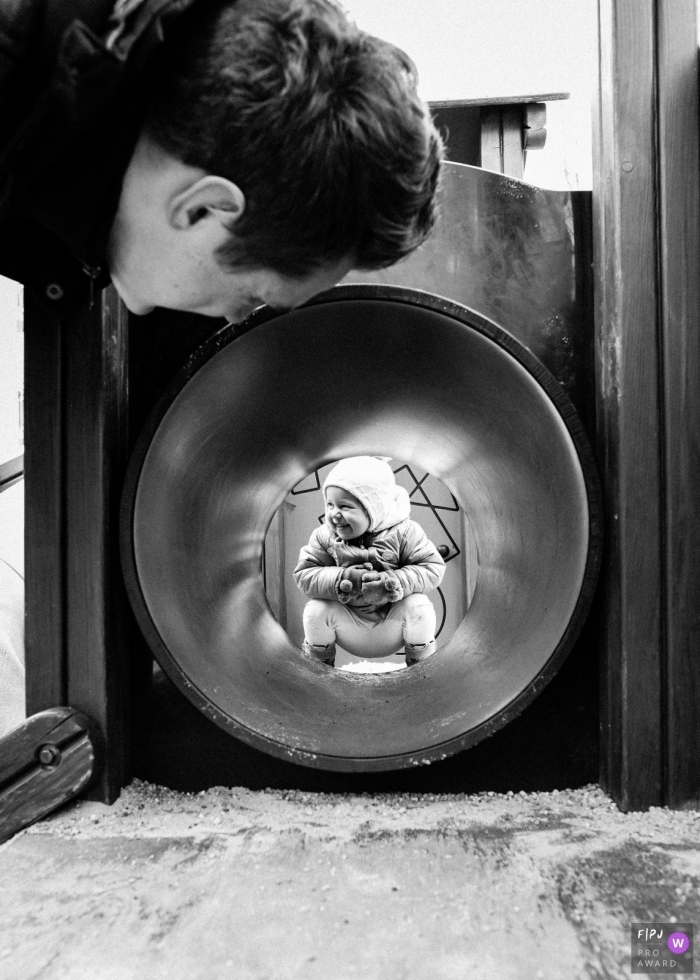 A father looks through a playground tunnel at his child in this black and white photo by a Lower Silesian family photojournalist.