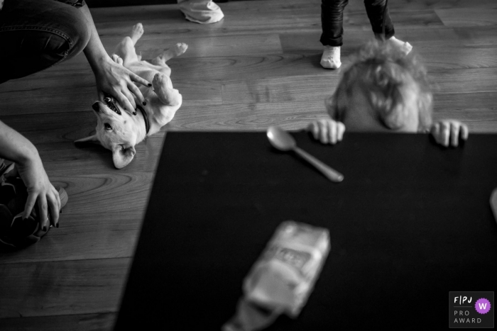 A mother pets a dog in the background as her daughter attempts to peek over a table in this black and white photo by a Dusseldorf family photojournalist.
