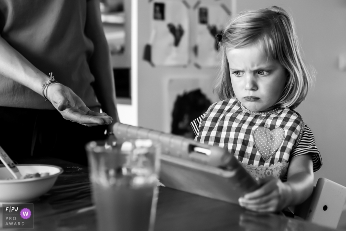 A little girl makes a face as her mother asks her to hand over the tablet she's playing on in this black and white photo by a Netherlands family photojournalist.