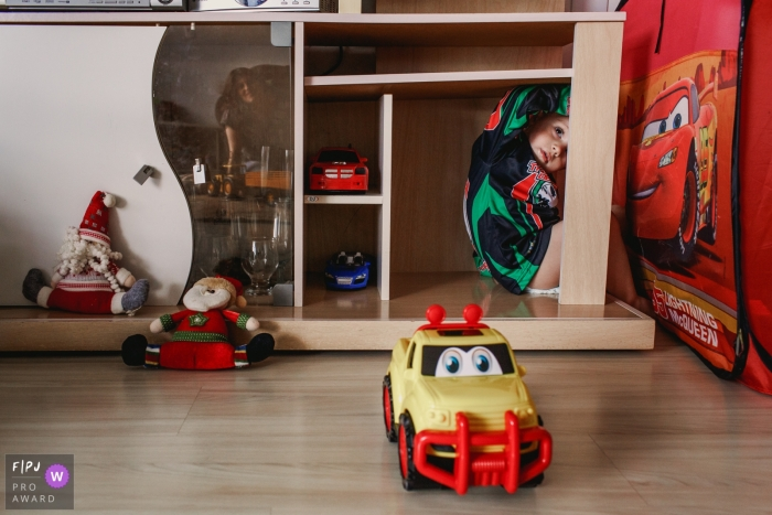 A little boy sits hiding on a shelf surrounded by toy cars in this photo by a Rio Grande do Sul, Brazil family photojournalist.