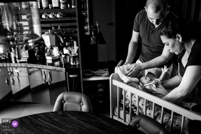 A mother and father put their baby in a crib in this black and white photo by a Rio Grande do Sul, Brazil family photojournalist.