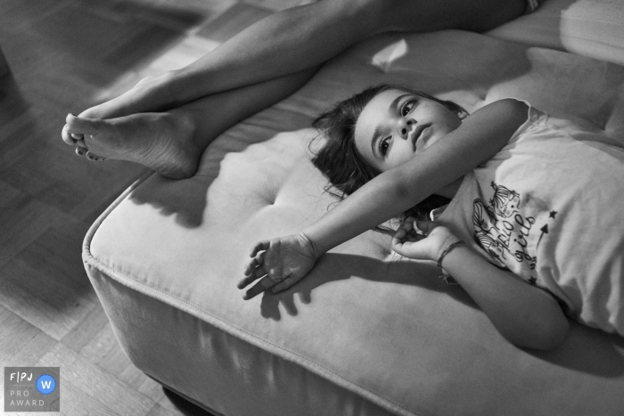 A girl lays on an an ottoman next to her mother's legs in this black and white photo by a Rome family photographer