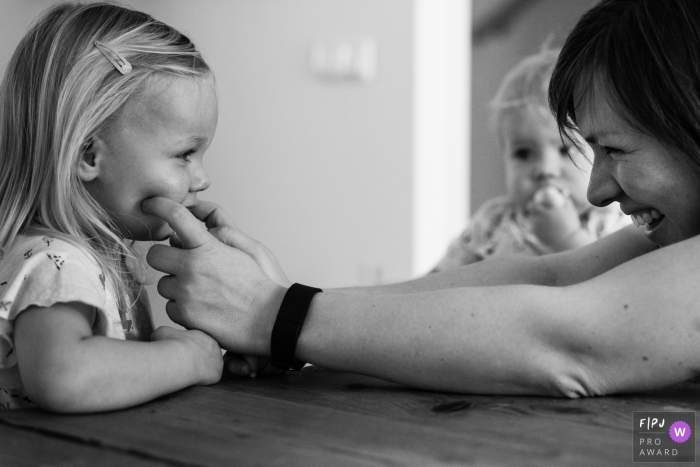 A mother pinches her daughter's cheeks in this black and white photo by a Netherlands family photojournalist.