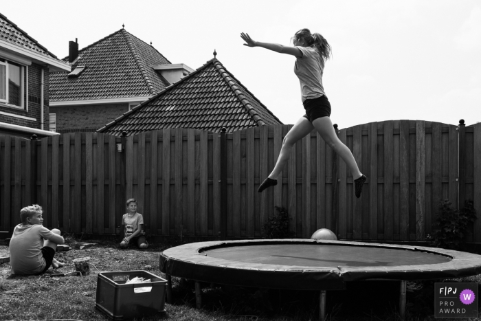 Two young boys watch their mother jumping on a trampoline in this black and white photo by a Netherlands family photojournalist.