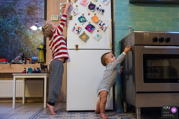 A young boy and his baby brother play with magnets on the refrigerator and stove in this photo by an Antwerpen family photojournalist.