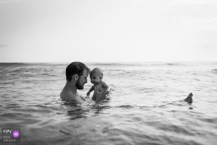 A man floats in the ocean holding his baby in this black and white photo by a Rome family photojournalist.