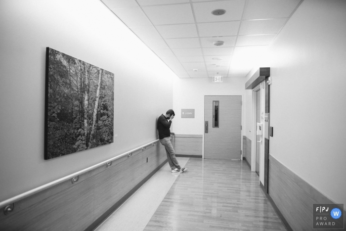An anxious soon-to-be father leans against a hospital wall covering his face with his hand in this black and white photo by a Seattle, WA birth photographer.