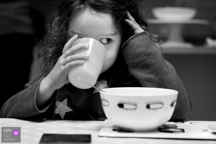 A girl sips from a cup as she eats her breakfast in this black and white photo by a Gloucestershire, England family photojournalist.