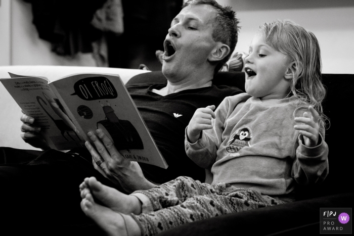 A father and daughter excitedly read a book together on a couch in this black and white photo by a Gloucestershire, England family photojournalist.