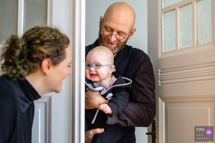 A wife smiles at her husband and their baby who wear matching glasses in this photo by a Berlin, Germany family photojournalist.