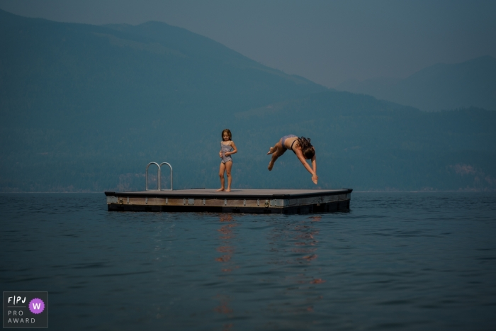 A girl dives into a lake as another stays on the dock in this photograph by a BC family photojournalist.