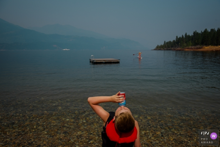 A boy sits on a lake shore taking a drink in this photograph created by a BC family photographer