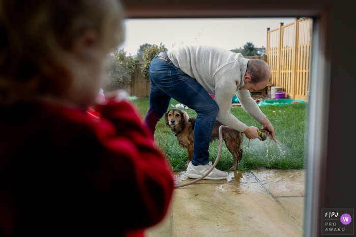 A little girl watches her father hose down their dog outside in this photo by a Kent, England family photojournalist.