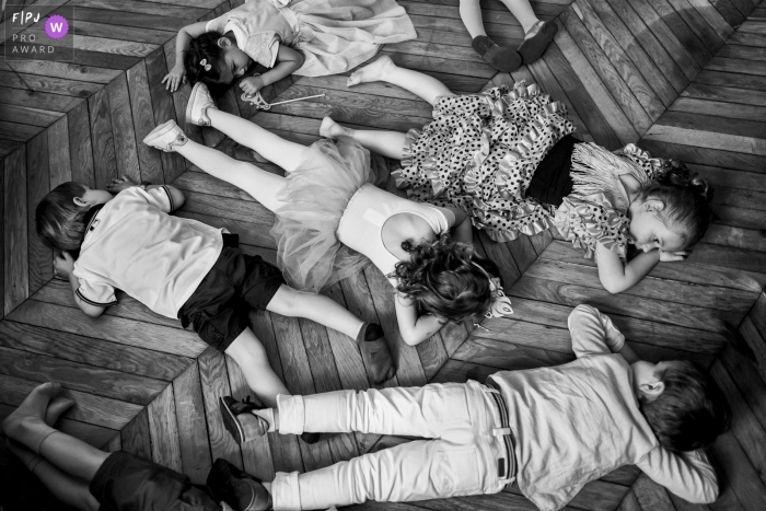 Several children lay on their stomachs on a wood floor in this black and white photo by a France family photojournalist.