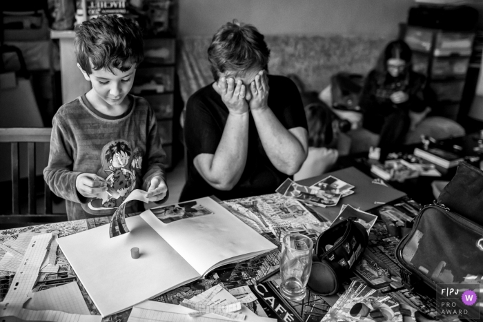 A mother covers her eyes as her son helps put a scrap book together in this Family Photojournalist Association award-winning photo by a France documentary family photographer.