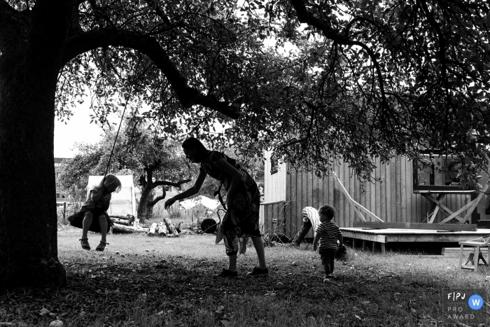 A mother pushes her daughter on a tire swing hanging from a large tree in this black and white photograph by a Netherlands family photojournalist.