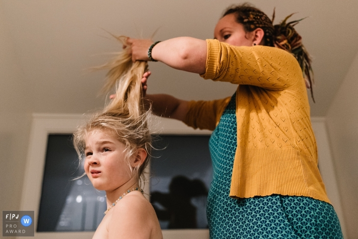 A mother works on putting her daughter's hair in a ponytail in this photo by a Gelderland, Netherlands family photojournalist.
