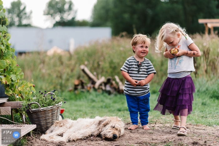 A boy and girl walk together outside as a dog lays down on the ground in front of them in this photo by a Gelderland, Netherlands family photojournalist.
