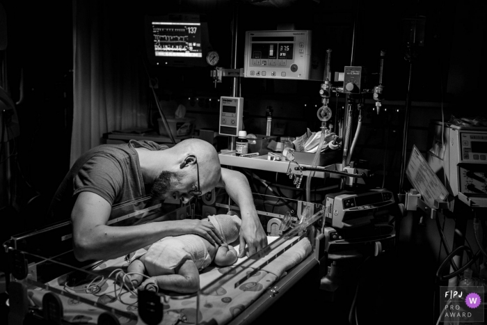 A father puts his hand on his baby's back in the hospital in this black and white photo by a Groningen, Netherlands birth photographer.