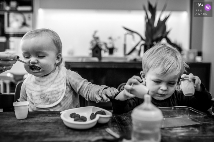 A little boy plays with yogurt cups as his mom feeds his baby brother in this black and white photo by a Savoie family photojournalist.