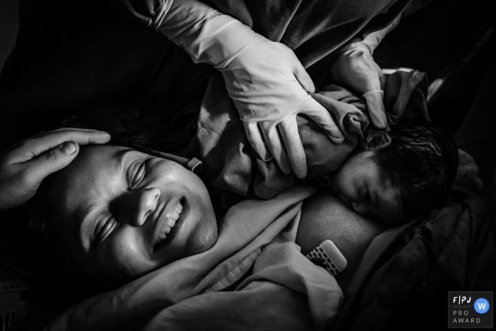 A doctor helps a baby nurse for the first time in the hospital as the mother smiles in this black and white photo by a Manaus birth photographer.