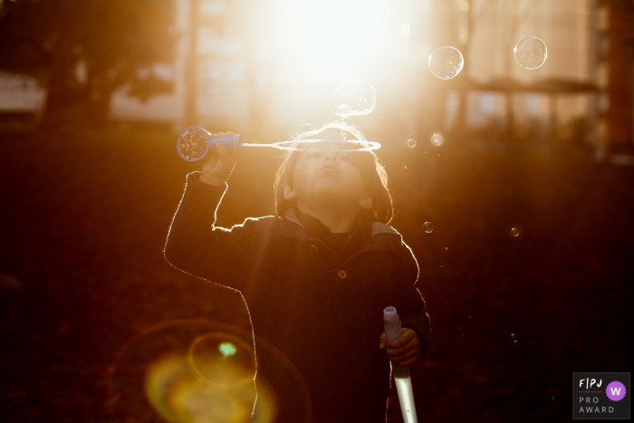 A child blows bubbles outside surrounded by sunlight in this photo by a Rio Grande do Sul, Brazil documentary-style family photographer.