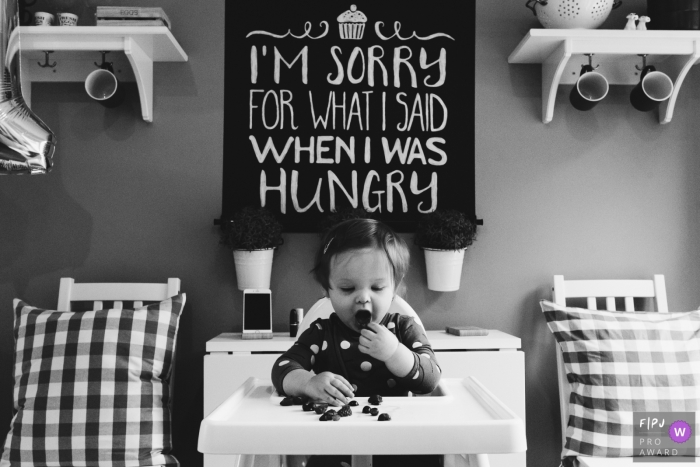 A little girl sits in her high chair eating berries in this black and white photo by a Northumberland, England documentary-style family photographer.
