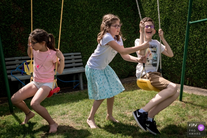 Three children play on a swing set outside in this photo by a Nantes family photographer.