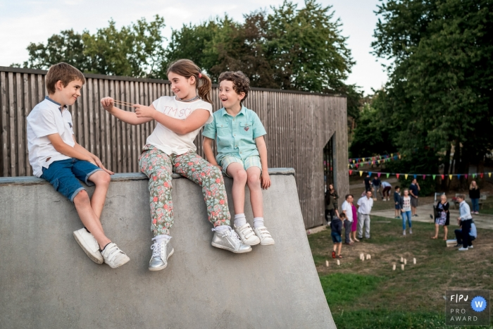 Three children sit on a skateboard ramp as the little girl pretends to fling a rubber band at one of the boys in this FPJA award-winning image by a Nantes family photographer.