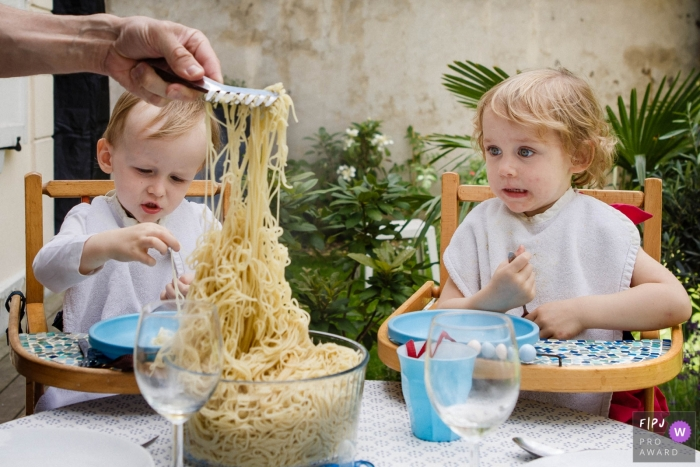 Two children wait eagerly in their high chairs as their father scoops pasta from a bowl in this winning picture by a Paris, France family photojournalist.