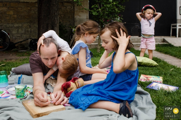 Paris family photojournalist captured this photo of a father enjoying a picnic with his children in the yard
