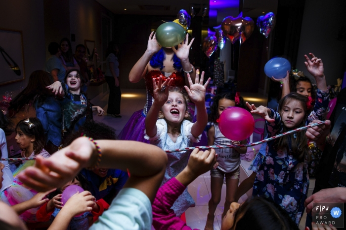 A large group of children run around playing with balloons in this photo by a Sao Paulo, Brazil award-winning family photographer.