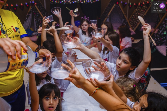 Several children hold up their cups to get refills as they sit around along table in this photographic image by a Sao Paulo, Brazil family photojournalist.