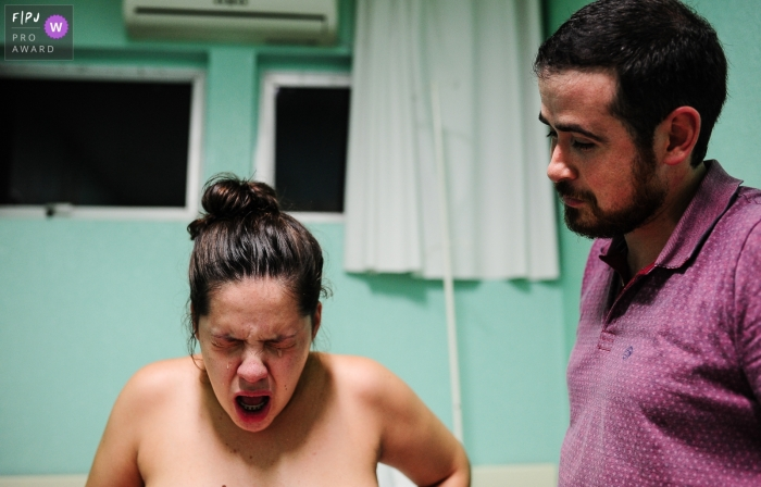A husband stands next to his wife as she gives birth in this photo by a Rio Grande do Sul, Brazil birth photographer.