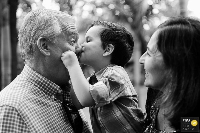 This black and white documentary family photograph of a toddler kissing his grandfather on the nose was captured by a 	Rio Grande do Sul photographer