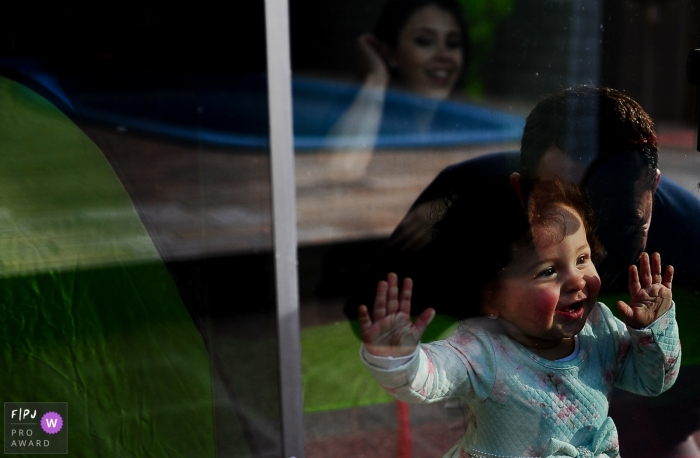 A little girl looks out the window at her father outside in this award-winning photo by a Rio Grande do Sul, Brazil family photographer.
