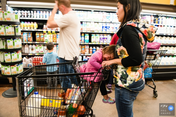 A little girl cries as her mother shops in the grocery store in this picture captured by a Los Angeles, CA family photojournalist.