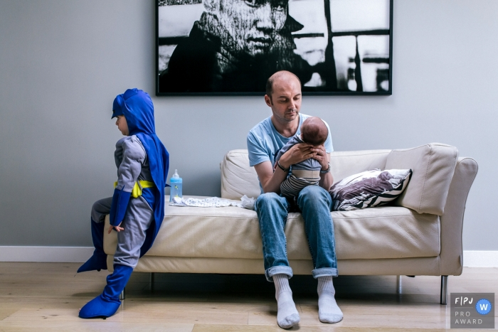 A father holds his infant as his older son sits on the couch in a Batman costume in this photo by a Paris, France award-winning family photographer.