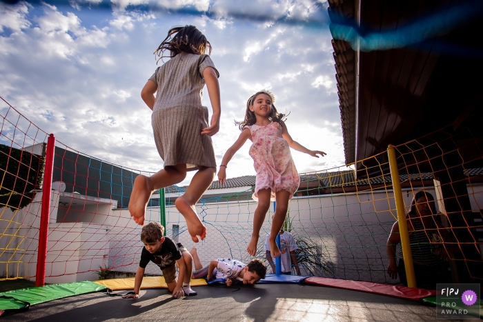 Four children play on a trampoline in this Family Photojournalist Association contest awarded photo created by a Sao Paulo, Brazil family photographer.