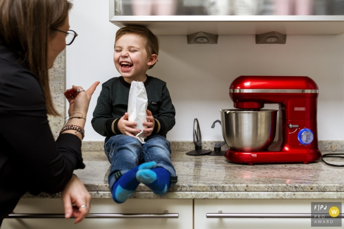Noord Holland family photojournalist captured this image of a happy toddler sitting on the kitchen counter while holding a bag of treats