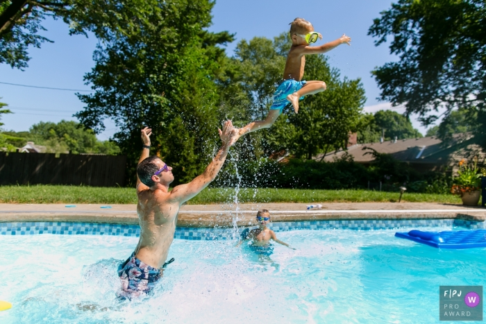 A father throws his sun in the air in a pool in this family picture by an Overland Park, KS photographer.